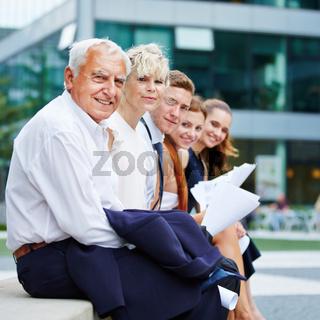 Business Team sitzt vor Büro