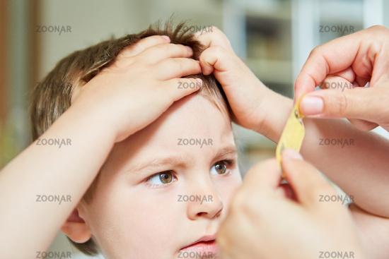Kind bekommt Pflaster auf Beule an Stirn beim Kinderarzt