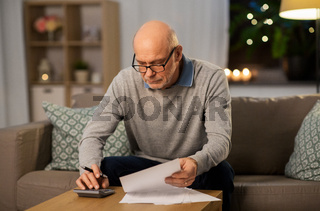 old man with bills counting on calculator at home