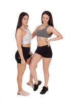 Two beautiful women standing in shorts in the studio