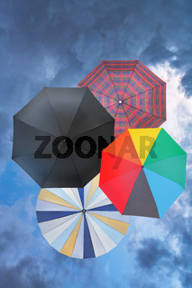 four open umbrellas with blue rainy clouds