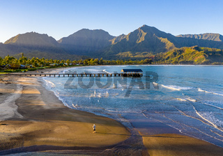 Aerial drone shot of man on the sand of Hanalei beach on the north shore of Kauai in Hawaii