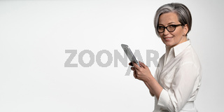 Cheerful business woman works on digital tablet on white background. Mature lady in white shirt looking at camera. Horizontal blank with empty spase for text at left side. Business or Education concept
