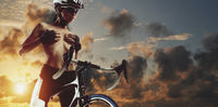 Sexy cyclist woman cover breast posing topless wearing sportswear helmet glasses standing with road bike on cloudy fluffy sky background bright sunset backdrop scenic view, copy pace for concept text