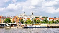 Ship anchored on Odra River embankment. Castle of Pomeranian Dukes in Szczecin in background