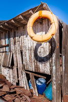 Old orange life saver hanged on edge of roof of shabby small wooden building among lot of boards