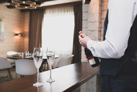 Man opens a bottle of sparkling wine. Two glasses stand on bar counter. The action takes place inside the cozy hotel room