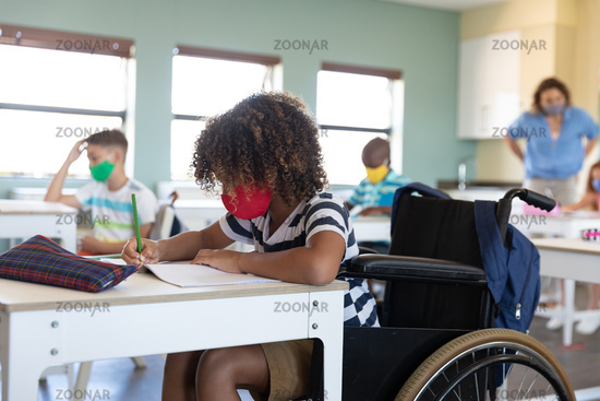 Disable boy wearing face mask writing while sitting on his wheelchair in class