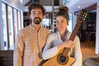 Woman holding classical guitar with man