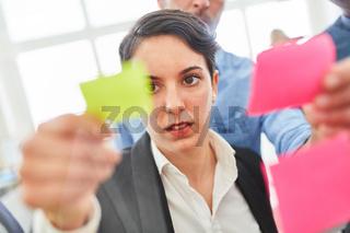 Frau schaut auf einen Zettel mit Projekt Ideen