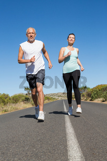 Fit couple running on the open road together