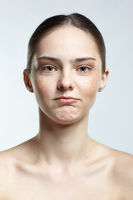 Headshot of emotional female face portrait with offended facial expression.
