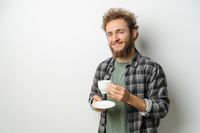 Smiling handsome man with curly hair and beard drinking coffee holding cup, wearing plaid long sleeve shirt isolated on white background