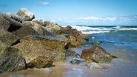 Felsbrocken als Wellenbrecher am Strand von Niechorze