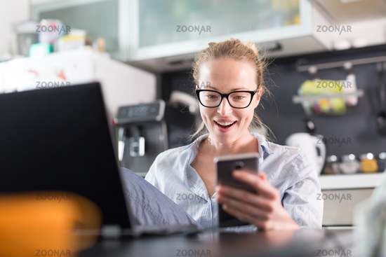 Stay at home and social distancing. Woman in her casual home clothing working remotly from kitchen dining table. Video chatting using social media with friend, family, business clients or partners