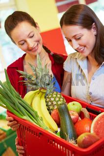 Mutter und Tochter kaufen Obst und Gemüse
