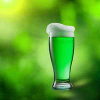 Glass of green beer on a blurred natural background.