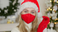 Portrait of a beautiful woman in christmas hat. The woman wears the protective mask from the virus