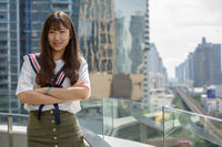 Happy young beautiful Asian teenage girl with arms crossed against view of the city