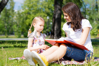 girl and a young woman reading a book together