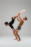 Couple of gymnasts performing acrobatic trick in studio