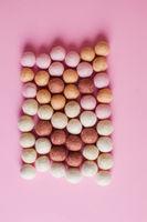Large amount of felt balls on pink background