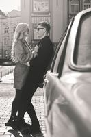 Lovely couple in sunglasses stay near the car.