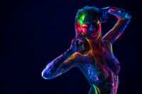 Pretty topless woman with neon ultraviolet body dance in dark