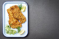 Traditional deep fried Wiener schnitzel from veal topside with cucumber salad and lemon slices offered as top view on a white tray with copy space right