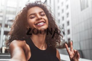 Pretty mixed race woman taking a selfie in modern city