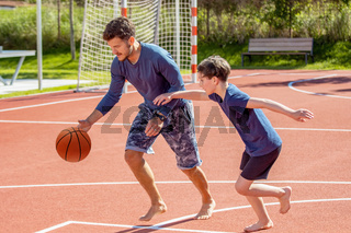 Dad and son playing basketball on a playground