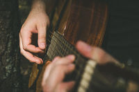 Fingers forming a chord on a guitar fingerboard. Male hands playing on guitar. Selective focus