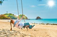 Woman on beach swing
