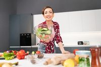 Happy young housewife holding bawl of salad showing it on camera prepared for a family dinner or girls night standing in the kitchen. Healthy food living. Healthy lifestyle