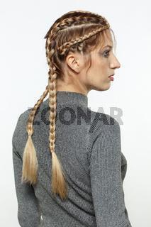 Portrait of blonde female with creative braid hairdo.
