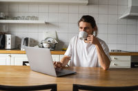 Freelancer working from home on the kitchen and using laptop. Handsome smiling man holding cup of coffee and looking at laptop. Successful self entrepreneur sitting with laptop and working at his modern home.