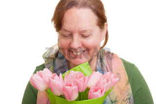 Elderly woman holding a bouquet of colorful pink tulips, smelling and  looking down, isolated on white background. Mothers day, Valentines day, Easter and surprise Concept.