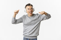 Portrait of handsome, modern middle-aged man, listening music in headphones and dancing, standing over white background