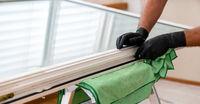 facility management cleaner cleaning a window and window frame with green micro fiber cloths