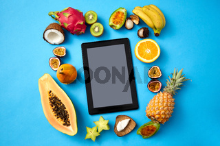 fruits around tablet computer on blue background