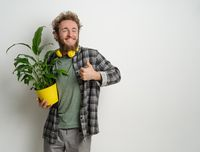 Young handsome bearded man holding yellow flower pot with plant in it dressed in plaid shirt and yellow headphones on his neck isolated on white background. Moving concept