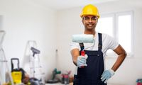happy indian painter or builder with paint roller