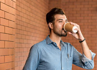 Caucasian businessman drinking coffee from takeout disposable coffee cup