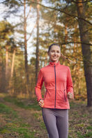 Healthy fit young woman jogging in woodland