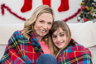 Festive mother and daughter wrapped in blanket