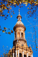 Ancient architecture tower view in Plaza de España against blue sunny clear sky framed by tree leaves. Main landmark popular place for tourists, travel destinations. Seville city, Andalusia, Spain