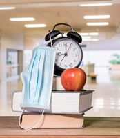 Back to school background concept with stack of books, alarm clock, apple with face mask