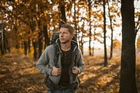 Young Backpacker Walking In Autumn Forest