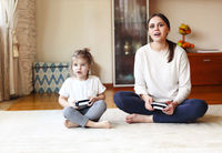 Happy mother and little daughter playing video game together