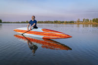 senior male stand up paddler enjoying sunrise